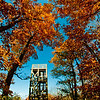 Blazing autumn foliage and blue skies umbrella hikers near the Summit Peak Observation Tower within Summit Peak Scenic Area and Porcupine Mountains Wilderness State Park (USA MI Ontonagon)