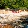 Expert open canoeist Boofing Sullivan Falls at a river flow of 744 CFS on the wild Wolf River Section 4 within Menominee Indian Nation  (USA WI Keshena)
