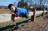 4/12/2014 Mike Orazzi | Staff Michael Beaucar,5, lays on a fence while waiting for the opening ceremonies to begin at the Forestville Little League in Bristol Saturday morning.