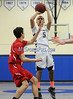 2/19/2014 Mike Orazzi | Staff Newington's Edwin Gomez (5) and Conard's Travis Sinatro (21) at NHS on Wednesday night.