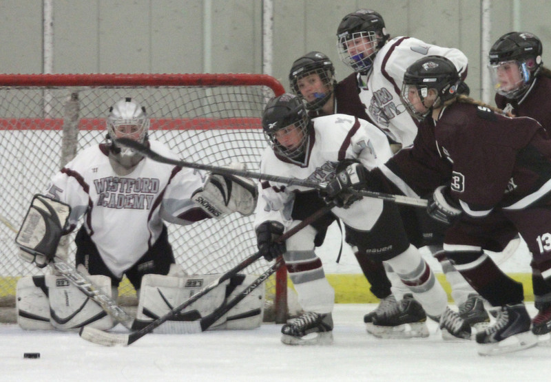Westford Academy vs Chelmsford girls hockey. Westford Academy's Kelsey Doran (16), center, helps clear the puck away from Chelmsford's Julia Squeri (13), right, with WA's Kerry Pouliot (25) in goal. (SUN/Julia Malakie)