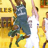 Elyria Catholic's DJ Graham leaps to shoot past Avon's Brad Sprecher.  LINDA MURPHY/CHRONICLE