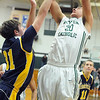 Elyria Catholic's Jeremy Holley puts up a shot over North Ridgeville's Tyler Arnold. STEVE MANHEIM/CHRONICLE