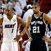 Miami Heat center Chris Bosh (1) and San Antonio Spurs forward Tim Duncan (21) stand on the court during the first half of Game 6  in their NBA Finals basketball series, Tuesday, June 18, 2013 in Miami. (AP Photo/Lynne Sladky)
