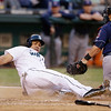 Seattle Mariners' Kendrys Morales slides across the plate after being tagged out by Cleveland Indians catcher Yan Gomes in the third inning of a baseball game Tuesday, July 23, 2013, in Seattle. (AP Photo/Elaine Thompson)