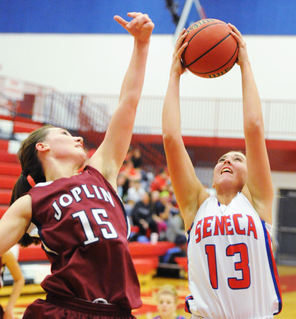Seneca's Bailey Skelton brings down the rebound ahead of Joplin's Kelsey Johnson Thursday night, Dec. 19, 2013, at Seneca High School's gymnasium. Globe | T. Rob Brown