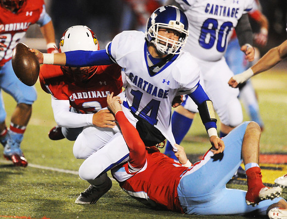 Carthage quarterback Gabe Franklin gets brought down by Webb City defenders Hunter Rhea (left) and Carson Johnson (below) Wednesday night, Nov. 6, 2013, at Webb City's field.<br /> Globe | T. Rob Brown
