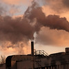 Air pollution by dark smoke coming out of two factory chimneys