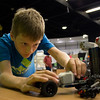 A boy makes adjustments to his Lego Mindstorms creation in the EPL Makerspace.  Taken on July 16, 2014 by James Cadden.