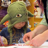 little girl in Yoda hat does crafts