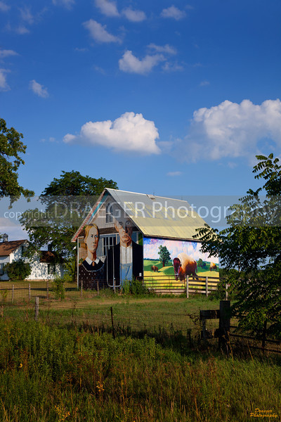 Less than a click away from the entrance to Palisades-Kepler State Park in Linn County is a small out-building draped in paintings of Iowa.  On the north side is a replica of the American Gothic by Grant Wood.