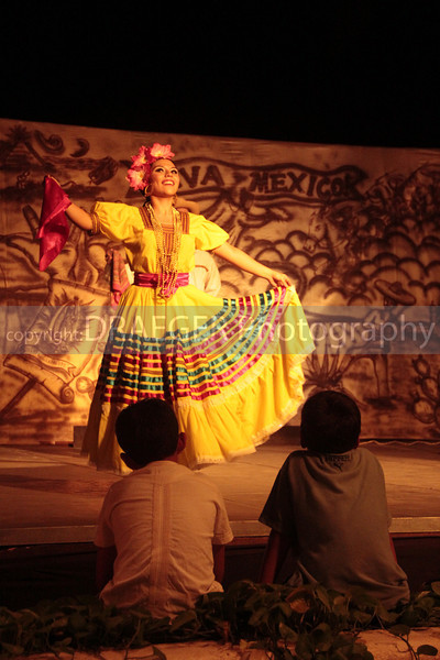 (Ixtapa, Mexico)  Two children interested in the dance sit as close to the stage as they possibly can.
