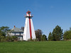 Red and white lighthouse on Prince Edward Island, Canada beside an old house,