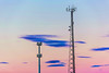 Silhouette in a pair of large transmission towers at sunset