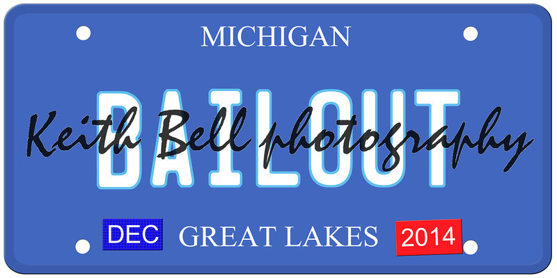 An imitation Michigan license plate with December 2014 stickers and BAILOUT written on it making a great Detroit or Michigan auto concept.  Words on the bottom Great Lakes.