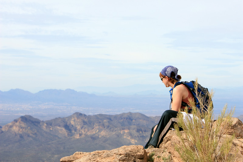 A yound girl admires the view after climbing to the top of a tall desert mountain