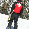 A ski patrol member carries a large drill to setup warning signs at a popular resort