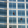 Three window washers descend on ropes high above the city. The building is a very modern glass structure.