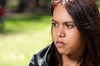 Teenage Indigenous Australian girl photographed outdoors.  She has a serious expression
