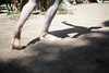 The lower body of an Aboriginal Male Dancer, featuring his shadow in focus