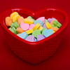 a close up shot of a heart shaped dish filled with heart candies on a red background.