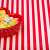 a heart shaped candy dish filled with heart candies left justified on a red and white striped background. copyspace