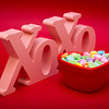 a wood carved X and O's symbol stands up on a red textured gradient background with a heart shaped candy dish full of candies in front