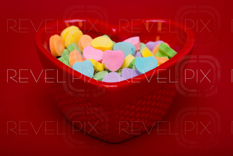 a close up shot of a candy dish filed with heart shaped candies on a red textured background. A pink candy heart is pointed at camera. fill with your own text