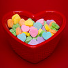 a vertical shot of a heart shaped candy dish filled with candies on a red textured background.