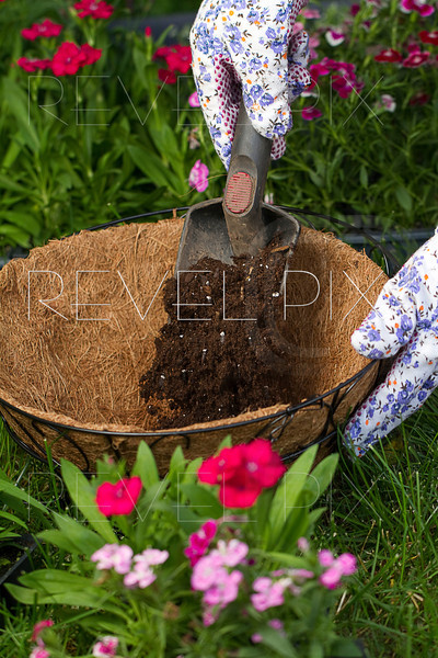 a gardener is filling up a coco lined hanging basket with potting soil.