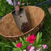 a gardener dumps some potting soil into a coco lined wire hanging basket.