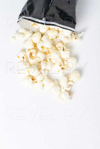 shot from above. a bag of white cheddar popcorn spills out of a bag. macro shot on white background in studio.