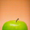 a plastic green apple with a orange polkadot background.