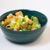 a studio lit shot of a traditional salad with croutons and cheese chunks in a green bowl