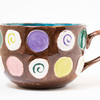 a macro selective shot of a hand painted mug in a studio. focus on side of mug