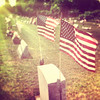 shot on iphone 4. edited in snapseed/instagram. flags wave in the wind on a headstone in a graveyard. lensflare, sun, slight texture