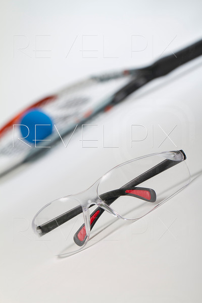 Racquetball safety glasses in foreground. Racquet and blue ball in background blurred. shot on white/gray background