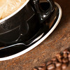 a freshly brewed Cappuccino is in the background with out of focus coffee beans in the foreground.