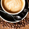 an above macro shot of a Cappuccino with coffee beans surrounding the cup. space below beans.