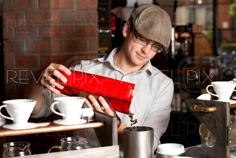 a cafe employee pours fresh coffee beans into grinder. focus on beans