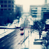A tilt shift shot of snowy traffic at an intersection with a blue tint and blur
