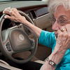 senior woman parked in car talking on cell phone