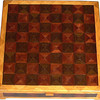 "CBox Ph-Wenge-Ash<br />    This Chess Box is about 13"" x 13"" and 3 5/8"" high on the outside. Inside it is 12 1/4"" x 12 1/4"" x 2"".  I made it using 612 pieces of wood cut in triangle shapes from different kinds of wood. Each square is 1 ½"" and is made by using four triangles. This makes a design within each square and gives it a completely different look. The box is finished in its natural color with 5 or 6 coats of a clear wiping varnish, rubbed in by hand. The pieces are a bit over 3/16"" thick, glued onto a Baltic Birch base, so they hold up much better than a thin veneer.<br />    The type of wood is listed on the bottom of the box from the center out. On this box the wood is ""Wenge"" from West Africa, ""Purpleheart"" from Central or South America and ""Ash heart wood"" from Missouri. <br />     On the bottom I signed it, listed the wood, and dated it.  <br />  <br />    I lined the bottom of the box with black velveteen."