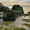 """27 Aug 14.  The furthest NW you can reach in WA state, and likewise in the contiguous 48 states, is Cape Flattery. It was named by Captain James Cook on 22 March 1778 during his search for the NW Passage because """"there appeared to be a small opening which flattered us with the hopes of finding an harbour ...""""  I believe this to be the only cape similarly named. The trail from the highway to this lookout point is easily traversed, takes about 15 minutes of walking on a very well maintained trail, and affords many magnificent views at its termination, as well as some nice views of heavily forested land along the way. The trail is not handicapped accessible, nor would folks with walking difficulties find it welcoming, but otherwise not difficult at all. The rocks, on the day and time of our visit, seemed to me to have a rather unusual texture to them, which may have been due to the evening lighting which was very contrasty in the cove. The camera did not record what I was sensing, and while what it recorded was likely a more accurate version of how the rocks actually are, the capture didn't come close to what I was experiencing. As such, in an attempt to convey what I was experiencing, I've increased the micro contrast of the rocks to render them closer to what I """"saw."""" When you visit I'll wager you see them very differently from what I saw when we were there. Nikon D300s; 18 -200; Aperture Priority; ISO 200; 1/1000 sec @ f / 8."""