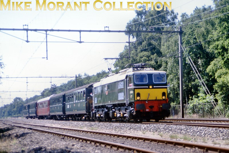 Preserved EM2 27000 <i>Electra</i> zips through Maarn (NS) on June 17th 1989. The stock is from the Stoomtram Hoorn Medemblik (SHM).<br> [<i>Slide taken by Mke Morant</i>]