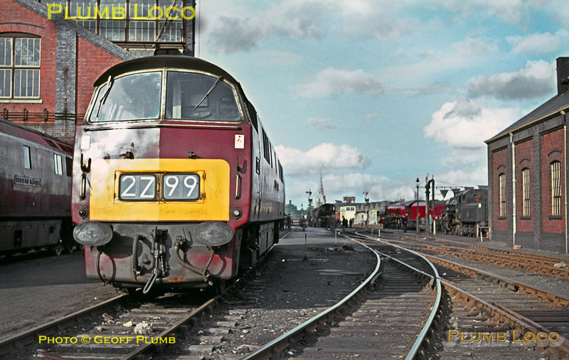 """Western"" Class 52 C-C diesel hydraulic No. D1018 ""Western Buccaneer"" sits outside Swindon Works alongside classmate D1013 ""Western Ranger"" (now preserved), both carrying BR Maroon livery. Also in maroon livery in the background is LMS Stanier ""Coronation"" class 4-6-2 No. 46251 ""City of Nottingham"" which was visiting with an RCTS railtour from Nottingham. Ivatt 4MT 2-6-0 No. 43056 is also in the background. Saturday 9th May 1964. Slide No. 675."