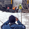 Westford fire and police stand by as workers from PanAm, (railroad), work on placing three tank cars and two box cars back on track in the Graniteville section of Westford, here a worker from EPA takes photos of the PanAm workers near the tank cars  .  SUN/ David H. Brow