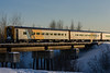 Ontario Northland train 622 crosses Store Creek bridge in Moosonee, Ontario on its way to Cochrane. Coaches 852, 856 and 841. Shot into the setting sun, highlighting impression of structural members through coach sides.