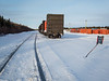Boxcars and four bulkhead cars with containers in Moosonee. Stop Men at work sign protecting track.