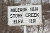 Sign for Store Creek in Moosonee. Mileage 186.04 from Cochrane, elevation 18 feet.